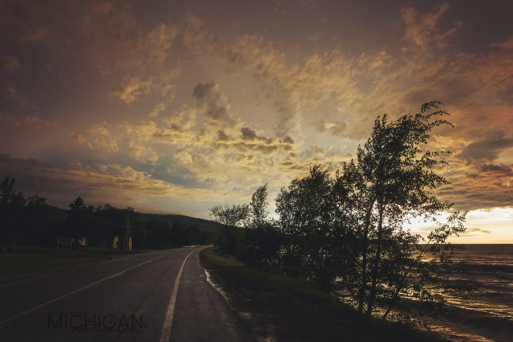 A sunset silhouettes the Road to the Porkies and Lake Superior on the right.